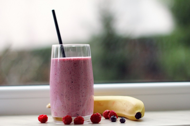 Pink Smoothies on a Window with a Banana and Berries