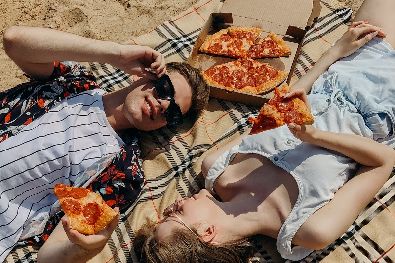 Surprising Reasons Why You Overeat a Couple Lying Down on a Beach Eating Pizza