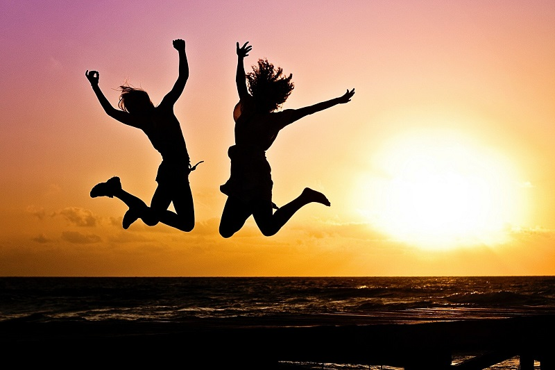 Tips to Reach Your Goals Two Peopl Jumping in the Air With the Sun Setting Behind Them