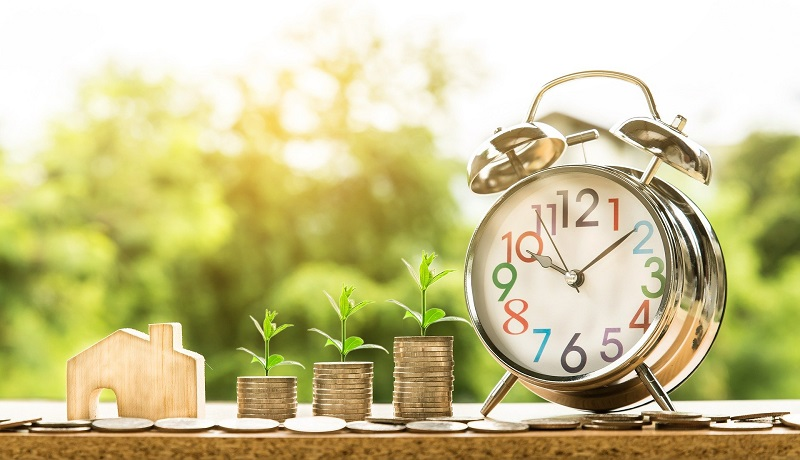 Tips to Reach Your Goals a Tiny House with Coins Stacked Up Next to It and an Alarm Clock