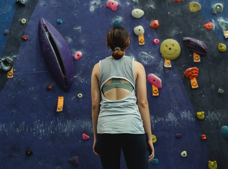 Ways To Make Goal Setting Not Suck Woman Staring Up a Rock Climbing Wall