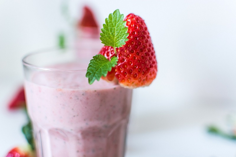Fat Burning Weight Loss Breakfast Smoothie Recipes Glass Filled with Pink SMoothie with a Strawberry on the Rim