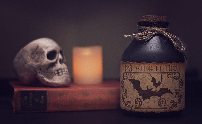 Healthier Halloween Cocktails A Jug of Poison on a Table Next to a Candle and a Skull