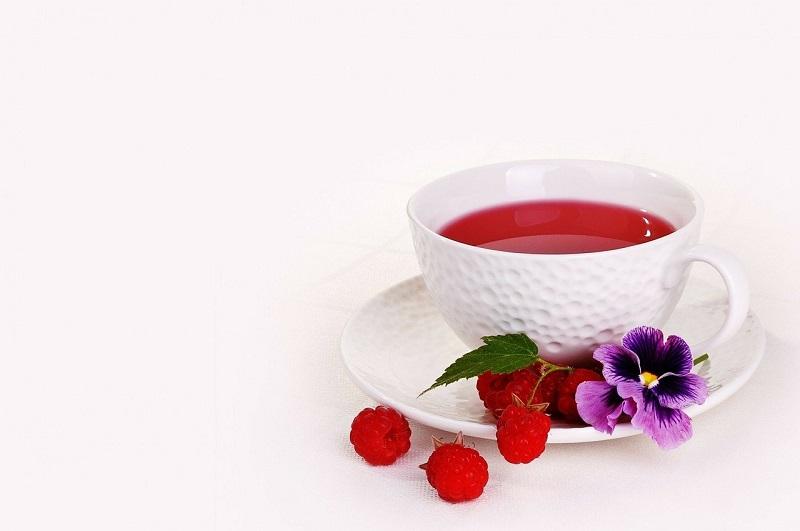 Herbalife Tea Flavors Cup of Raspberry Tea with Raspberries Around It
