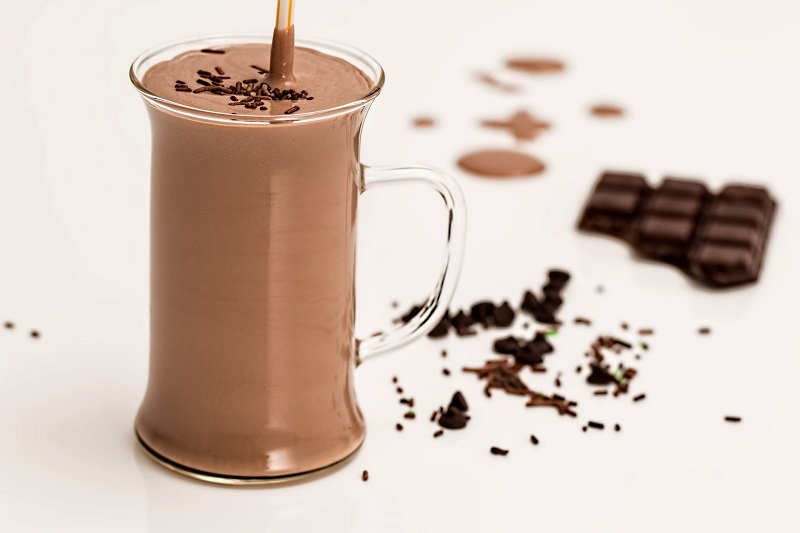Herbalife Healthy Weight Products Chocolate Shake in a Glass Mug with Chocolate Pieces Around it