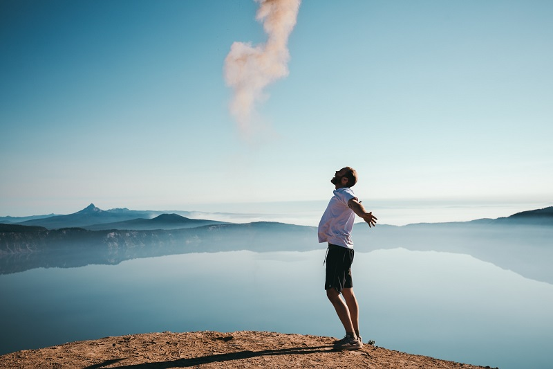 Herbalife Immune Health Benefits Man Standing on a Cliff with His Arms Spread Out