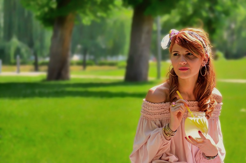 Herbalife Immune Health Products WOman at a Park Drinking Lemonade with a Flower in Her Hair