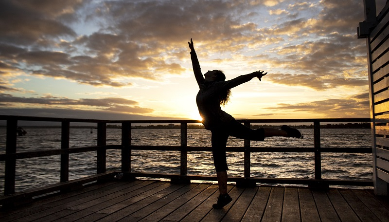 Herbalife Immune Health Products Woman Dancing on a Dock with the Sun Setting Behind Her