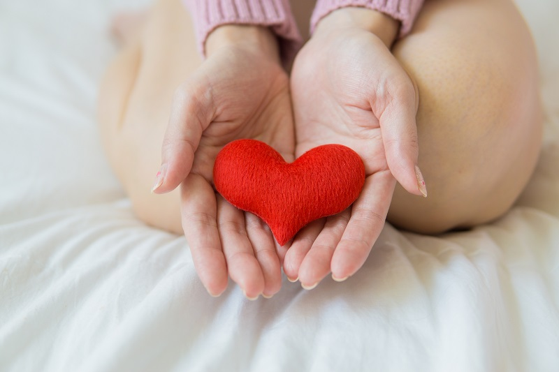 Herbalife Heart Health Benefits Woman Kneeling on a Bed Holding a Fabric Heart in Her Hands