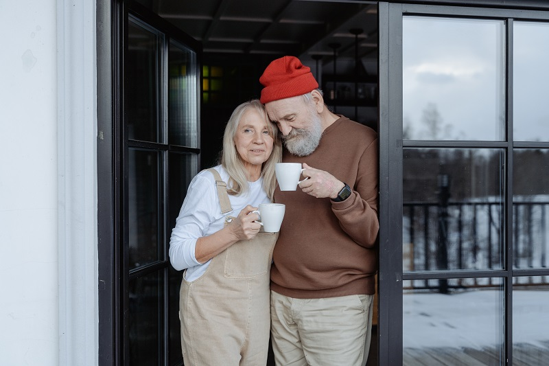 Herbalife Healthy Aging Product Benefits Elderly Couple Standing in a Doorway Drinking Hot Chocolate