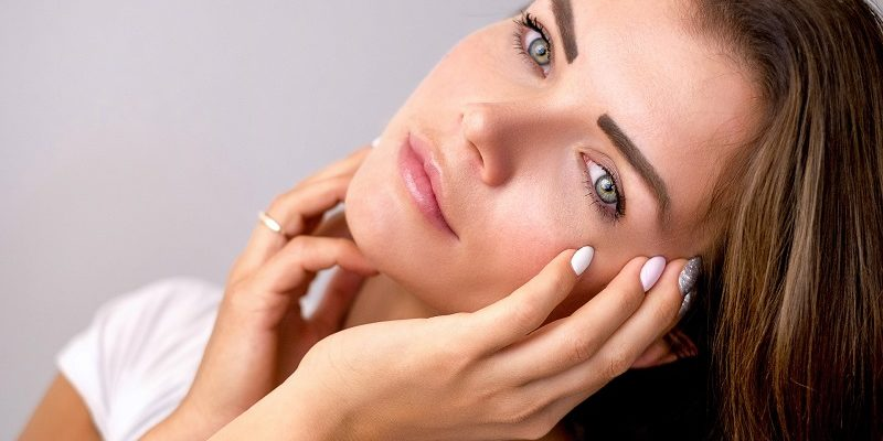 Benefits of Aloe in your Beauty Routine Woman Holding Her Face in Her Hand