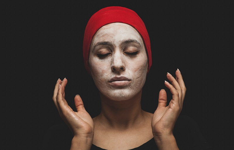 Herbalife Skin Products for Dark Spots Woman with a Facemask on and a Red Headband Holding Her Hair Back