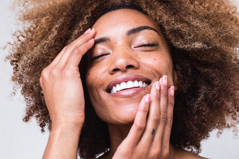 Herbalife Skin Product Benefits Woman Touching Her Face and Smiling