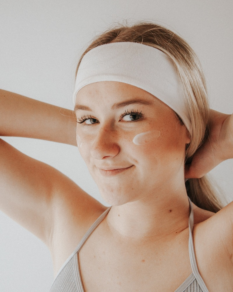 Herbalife Skin Products Woman Holding Her Hair Back with a Little Cream on Her Cheek