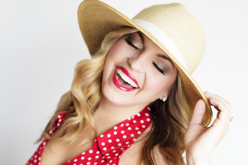 Herbalife Skin Products Woman in a Red Dress with a Hat Smiling